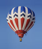 A Red, White, and Blue Hot Air Balloon. A patriotic hot air balloon drifts silently across a clear blue sky on a sunny spring morning Royalty Free Stock Photo