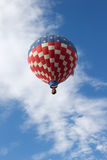 Red, White and Blue Hot Air Balloon. Flying in a blue cloudy sky royalty free stock photography