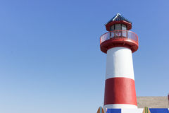 Red White and Blue Lighthouse. Lighthouse offset in picture to allow your words and images to merge into the blue sky background Stock Photo