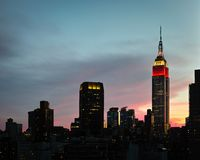 Red, white and blue lights on Empire State Building with nearby Stock Photo