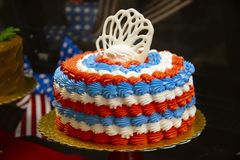 Red white and blue patriotic cake with bokeh holiday decorations behind and a chocolate cake blurred to the side royalty free stock photography