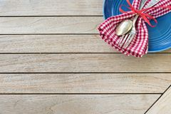 A Red White and Blue Picnic Table Place Setting with napkin, fork and spoon and plate in an upper corner on horizontal wood board. Table top background with stock photos