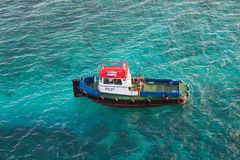 Red White and Blue Pilot Boat in Aqua Water. A red, white and blue pilot boat in the clear water of the Caribbean Stock Photos