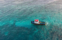 Red White and Blue Pilot Boat in Shallow Aqua Water. A red, white and blue pilot boat in the clear water of the Caribbean Stock Image