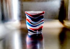 Red, white, and blue plastic cup casting shadows in a sink royalty free stock images