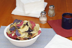Red, White and Blue Potato Chips. One bowl of red, white and blue potato chips on a kitchen table with linens, seasonings and beverage. Red, white and blue stock images