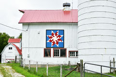Red, White and Blue Quilt Barn. A red, white and blue quilt barn in Walworth County, Wisconsin.  Patriotic star.  There is a fence and a silo and a metal red Royalty Free Stock Images
