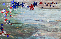 Red, White, and Blue Star confetti scattered on a rough wood background Stock Image