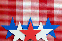 Red, white and blue stars border red checkered (gingham) background. Red, white and blue stars border red plaid fabric background Royalty Free Stock Image