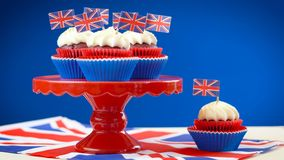 Red white and blue theme cupcakes and cake stand with UK Union Jack flags royalty free stock photography