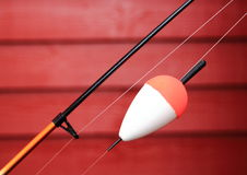 Red and white bobber on a fishing rod Royalty Free Stock Images