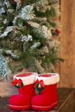 Red with white border Christmas boots under Christmas tree on wooden background.  Stock Photos