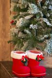 Red with white border Christmas boots under Christmas tree on wooden background. Red with white border Christmas boots under Christmas tree on wooden background royalty free stock photo