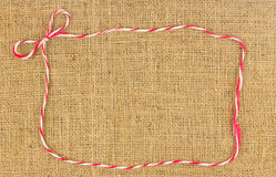 Red and white bow rope frame on brown hemp Royalty Free Stock Photography