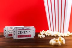 Popcorn With Two Red Movie Tickets. Red and White Bucket Of Popcorn With Two Red Movie Tickets/ Movie Night Close Up On Red Royalty Free Stock Photography
