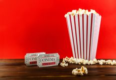 Popcorn With Two Red Movie Tickets. Red and White Bucket Of Popcorn With Two Red Movie Tickets/ Movie Night Close Up On Red Stock Image