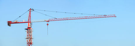 Red and white building tower crane against a blue sky. Jib crane Royalty Free Stock Image