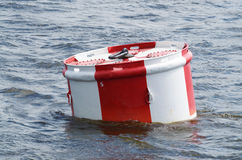 Red-white Buoy on the blue water. Serves as a landmark for ships royalty free stock images