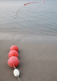 Red and white buoy on the sand and sea Royalty Free Stock Images
