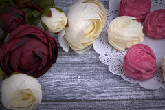 Red and white buttercup flowers ranunculus white and pink zephyr marshmallows lacy paper napkin on gray wooden background. Copy sp. Ace Stock Photo