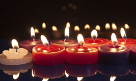 Red and white candles on a black background. Some red, white and purple candles glowing against a black background Royalty Free Stock Photos