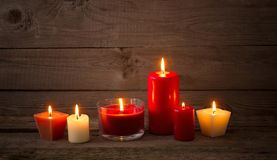 Red and white candles on dark wooden background Royalty Free Stock Image