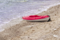 Red and white canoe on sandy beach, copyspace, nobody. Red and white plastic canoe on sandy beach, copyspace, nobody stock photo