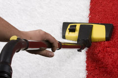 Red and white Carpet vacuuming. Tube cleaner on the carpet stock image