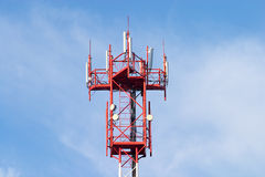 Red and white cellular tower with aerials on blue. Sky Stock Photos
