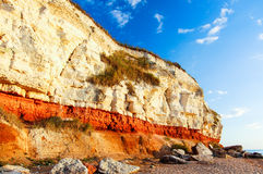 Red & white chalk cliff in Old Hunstanton, Norfolk. Beachside red & white chalk cliff. The lower reddish limestone known as red chalk is topped by a layer of Royalty Free Stock Photography
