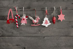Red white checked christmas decoration hanging on an old wooden Stock Photography
