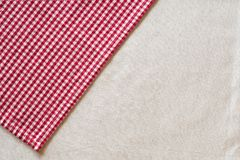 Red and White Checked Cloth at angle on upper corner of off white or cream colored linen table cloth. Horizontal above view with