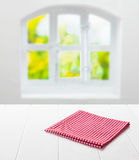 Red and white checked cloth in a country kitchen. Red and white checked cloth neatly folded on top of an empty clean white table top under a window with a view Stock Photo