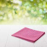 Red and white checked cloth on a garden table. Neatly folded fresh red and white checked cloth conceptual of a country or rustic ambiance on a garden table in a Stock Photo