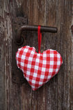 Red white checked heart hanging on an old door. Red and white checked heart hanging on an old door Stock Photography