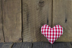 Red white checked heart on wooden background. Royalty Free Stock Photography