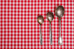 Red and white checked table cloth with old spoons Royalty Free Stock Images