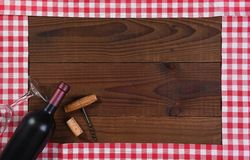 Red and white checked table runners forming a frame with a bottle of red wine. A glass and corkscrew royalty free stock photo