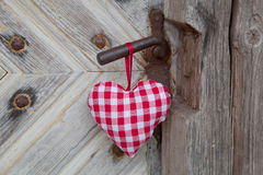 Red/white checkerd heart shape hanging on rusty door handle in c Stock Image
