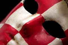 Red & white checkered carnival mask. Red & white checkered carnival mask black background close-up Royalty Free Stock Photography