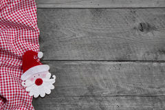 Red and white checkered fabric with santa head on wooden background Royalty Free Stock Photo