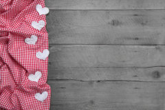 Red and white checkered frame with hearts on woode Stock Photography