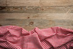 Red white checkered picnic tablecloth on wooden background, copy space. Red and white checkered picnic tablecloth on wooden background, copy space royalty free stock image