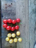 Red and white cherry tomatoes on wooden floor. Tomatoes, cucumbers and chili on rocks or wooden floor Royalty Free Stock Photo