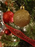 Red and white Christmas ball decorations. Gold Christmas ball decorations hanging on a Christmas tree with some red ribbon Stock Photo