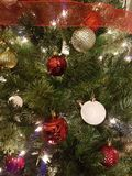 Red and white Christmas ball decorations. Hanging on a Christmas tree with some red ribbon royalty free stock images