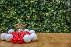 Red and white christmas balls next to a star on a wooden table. Red and white christmas balls next to a star, on a wooden table in a garden of a village house Stock Photo