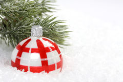 Red and white christmas balls on snow and icing pine branch. Horizontal Royalty Free Stock Photo