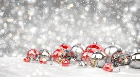Red and white christmas baubles lined up 3D rendering. Red and white christmas baubles lined up on grey snowy background 3D rendering Royalty Free Stock Photo