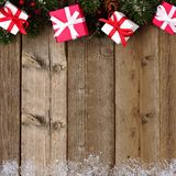 Red and white Christmas gift border with branches on wood Stock Image